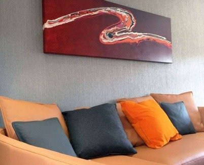 Orange sofa with orange and pink art above
