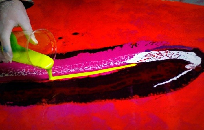Yellow paint being poured onto canvas