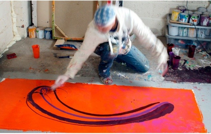 Pouring maroon paint quickly from a tumbler