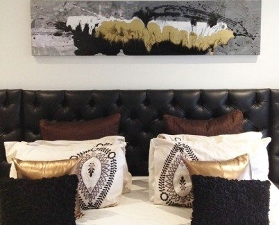 black quilt and gold cushions on a bed