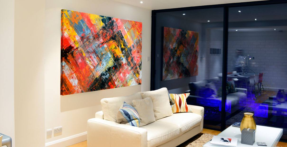 Big abstract painting hanging in a modern living room at night