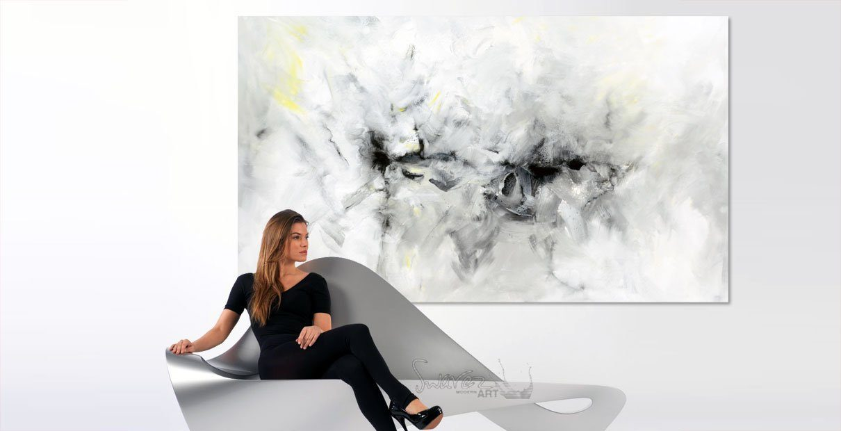 Girl on minimal sofa with art on the wall