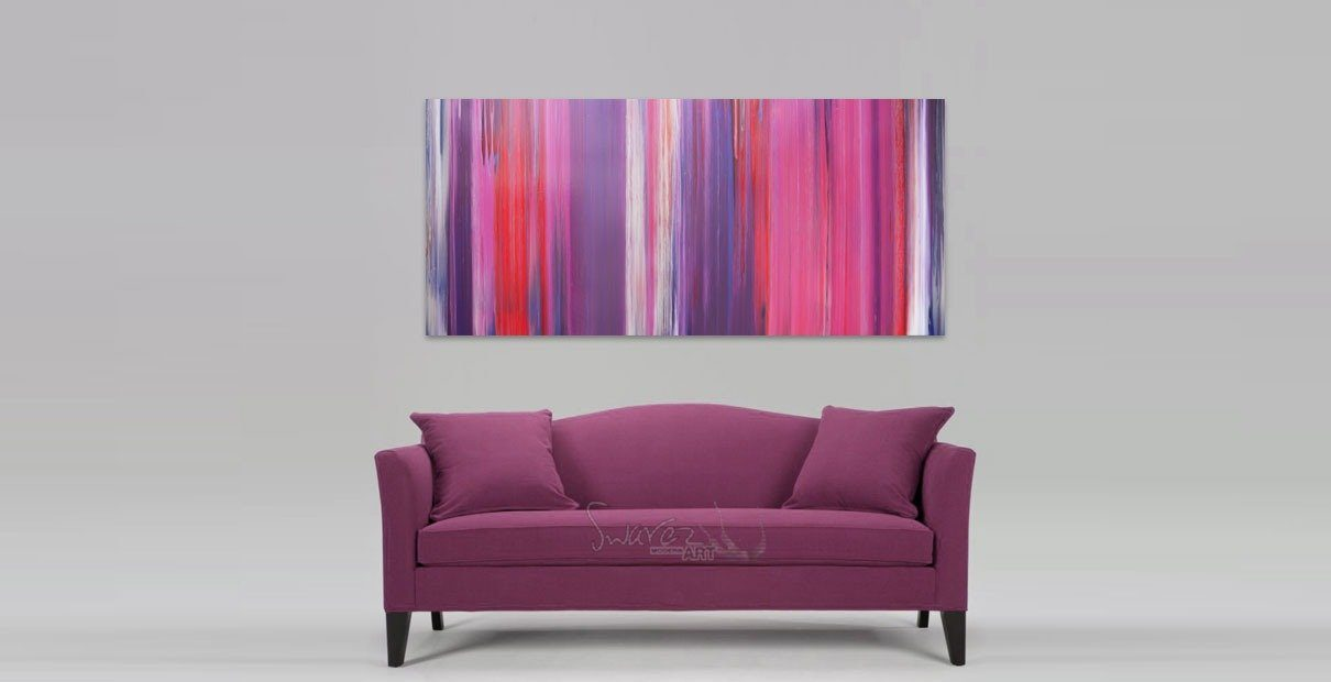 Pink art above a sofa