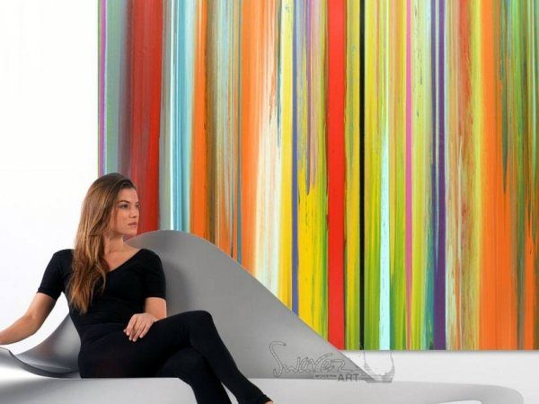 Woman on sofa and striped art behind her