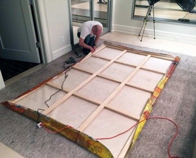 Finishing stretching a canvas painting on the floor