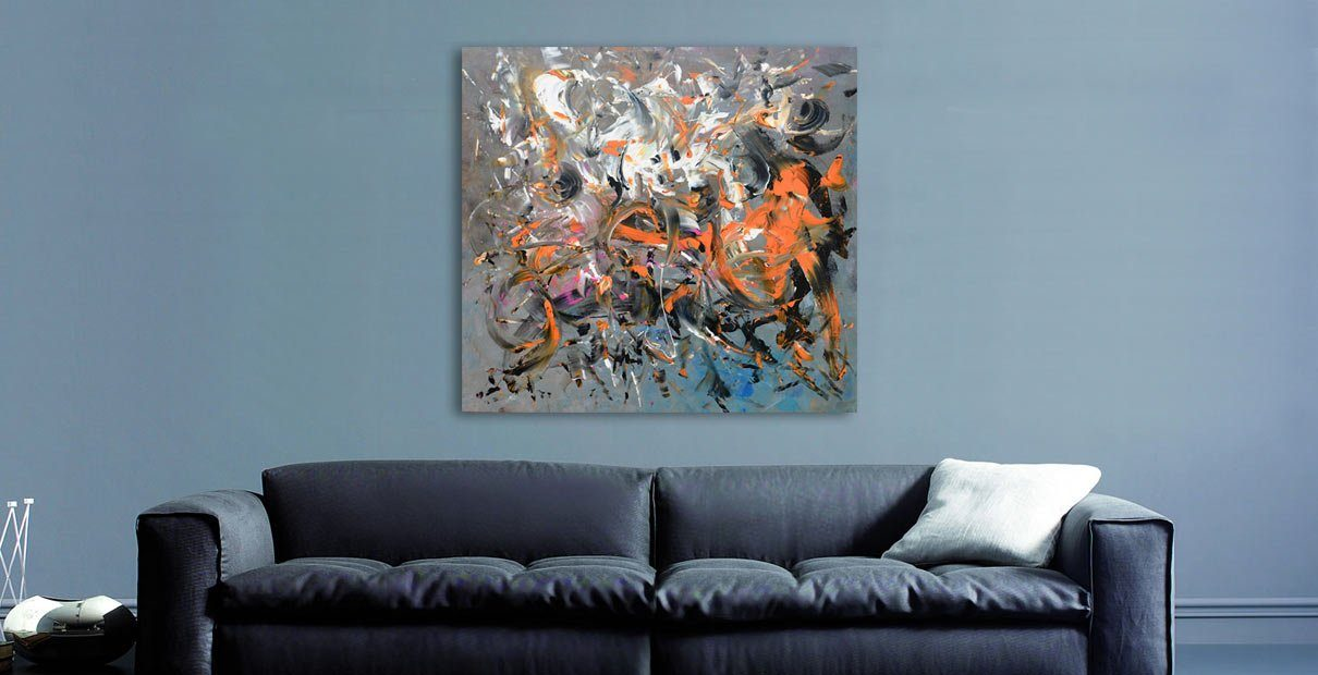 Square painting above a black sofa with a grey wall