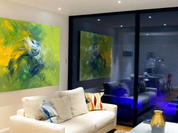Large green painting hanging in a contemporary living space