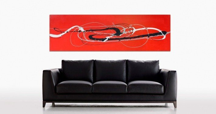 Red black and white art above a leather sofa