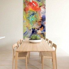 Colourful art hanging upright in front of a pine table and chairs
