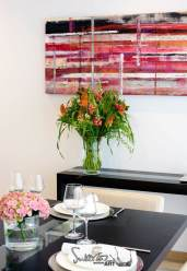 Black dining table, flowers and art hanging on the wall