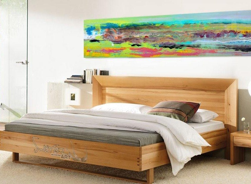 Brightly coloured painting above a bed