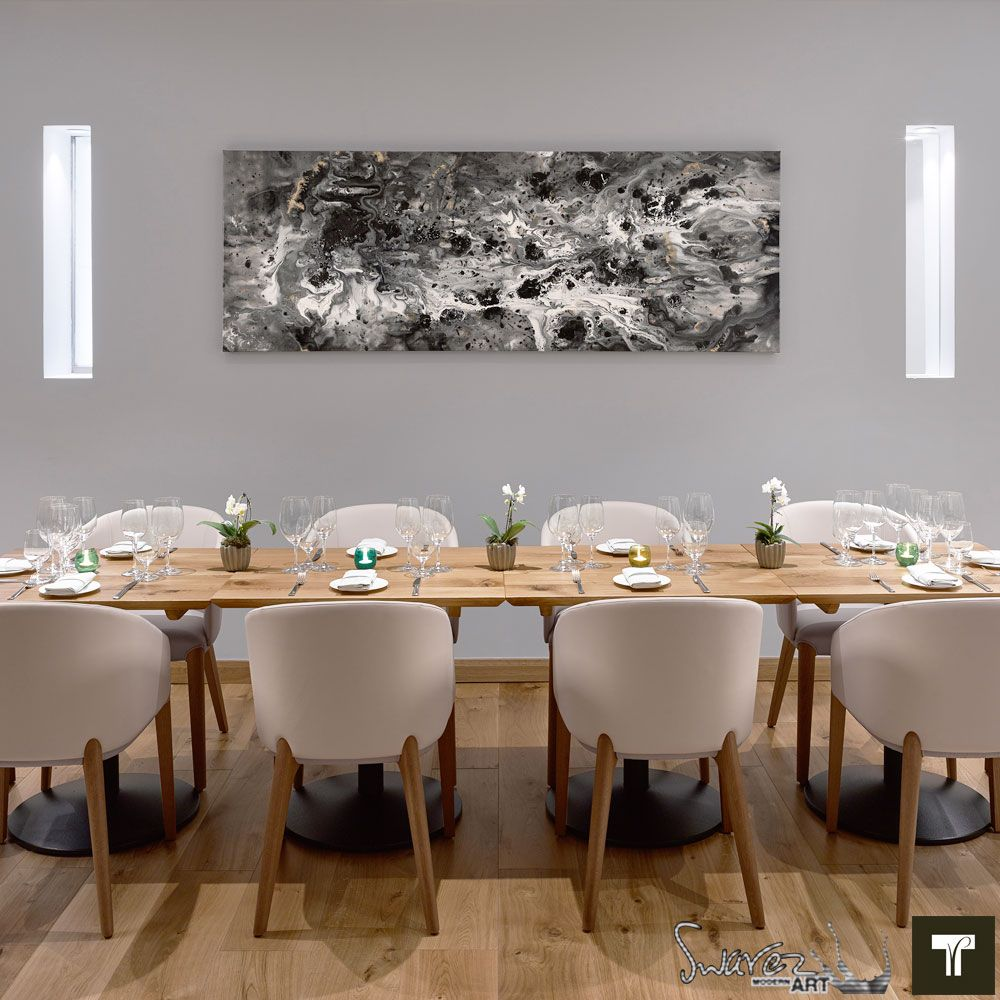 Restaurant dining table with black and white art hanging above it