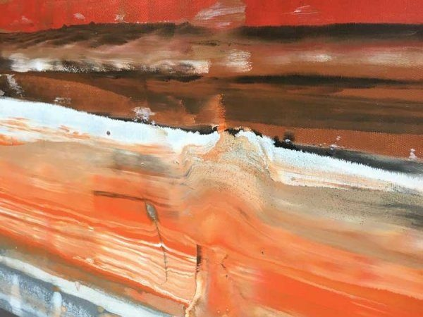 Orange lines of paint going across the surface of a canvas