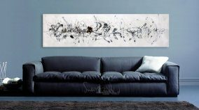 white and black art above a sofa on a grey wall