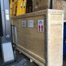 Fork lift truck lifting a wooden crate