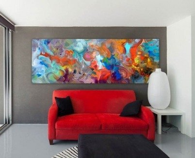Multi colored art above a red sofa in a modern living space