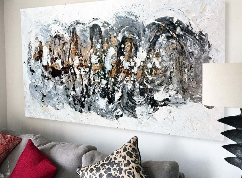 A medium sized black and gold abstract art painting above a sofa