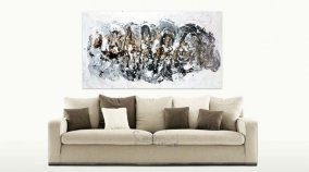 Beige sofa and black and gold art above it