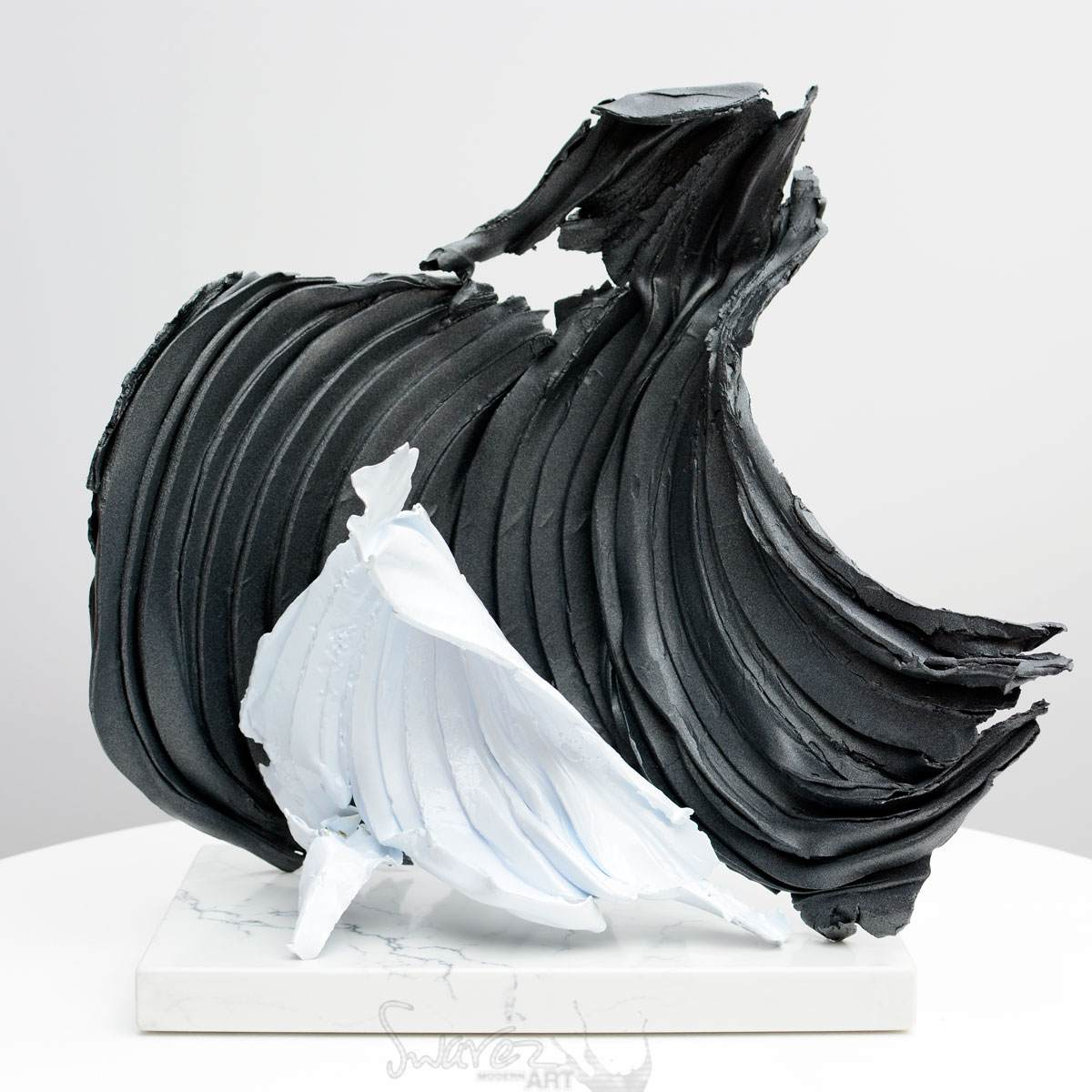 Grey and white metal sculpture on a white base