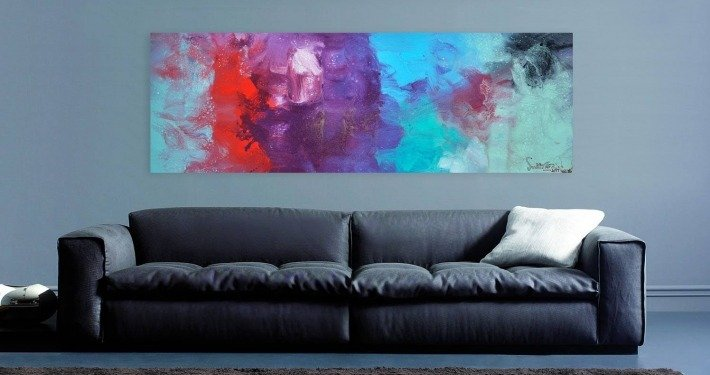 Grey walls and a sofa with abstract art hanging above it