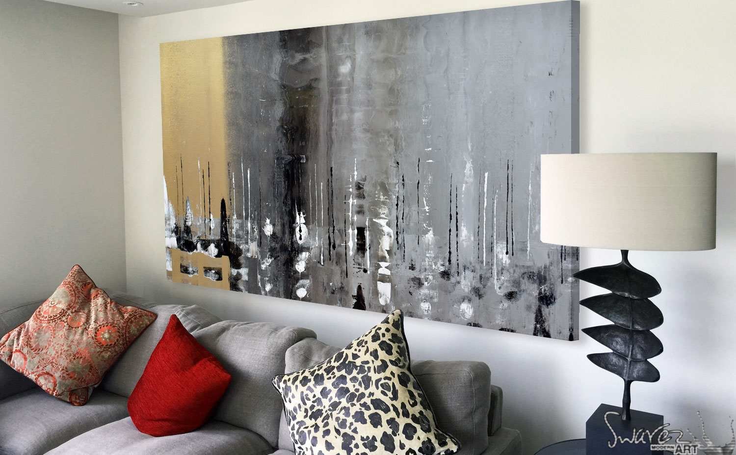 Gold and silver painting above a grey sofa