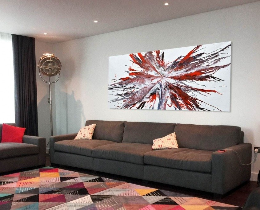 Red starburst art on a wall with a sofa
