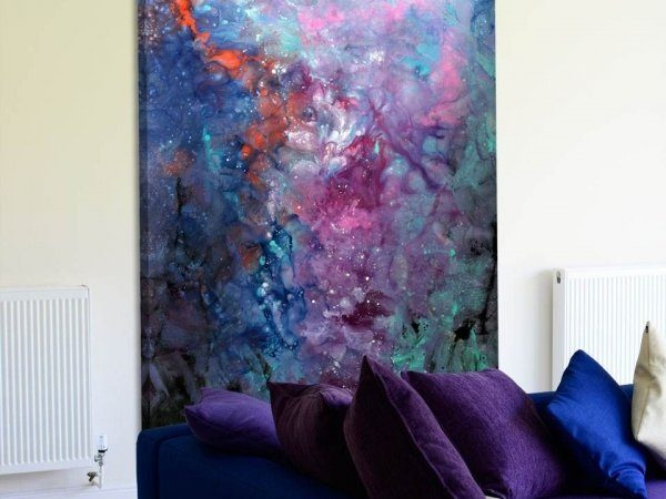 Pink and purple painting behind a sofa