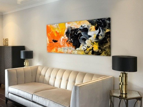 orange and yellow painting above a sofa