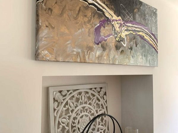 gold copper and purple modern art above fireplace