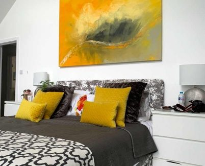 large yellow abstract painting above a bed