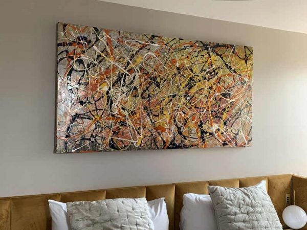 Jackson Pollock inspired abstract painting above a bed