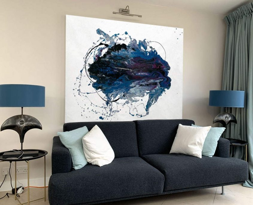 large minimal white and blue painting above grey sofa