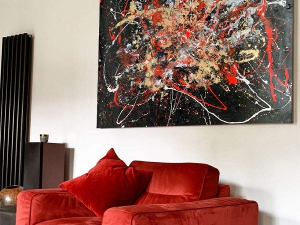 red armchair and red abstract art painting above