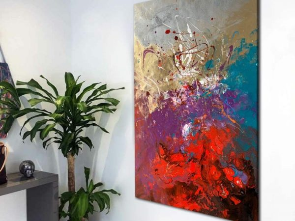 tall abstract painting in a hallway by a plant