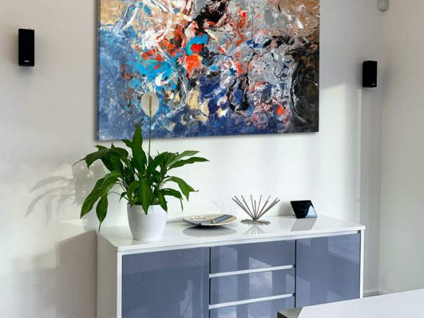 blue and gold art above a console table