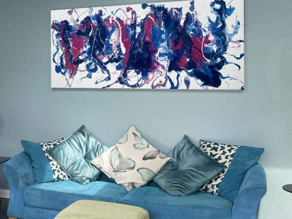 pink and blue abstract painting hanging above sofa